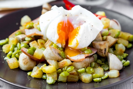 browns: Hot appetizer salad with potatoes, ham, green peas, mushrooms, poached egg with resultant yolk