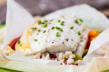 parchemin: Filet de poisson blanc cuit dans du papier, le parchemin avec du riz, des légumes, poivre, plat régime tatsy Banque d'images