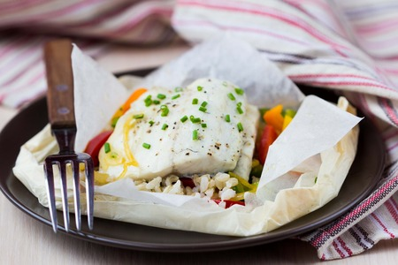 White fish fillet baked in paper, parchment with rice, vegetables, pepper, tatsy diet dish 版權商用圖片