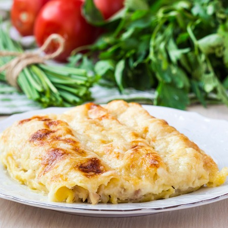 Italian pasta Cannelloni stuffed with meat, white Bechamel sauce, cheese crust, delicious dinner photo