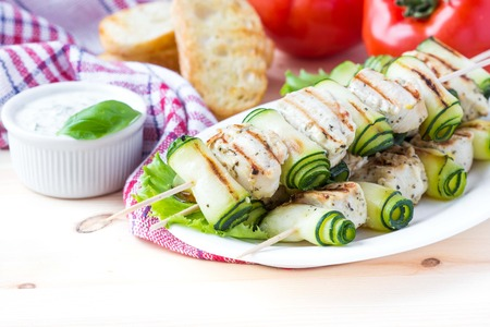 Grilled chicken filet kebab, shashlik on skewers with rolled zucchini, tasty picnic dish photo