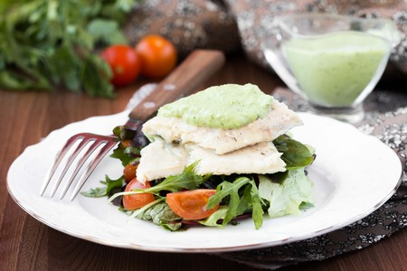 Fried white fish fillet with salad of lettuce, arugula, greens, tomatoes, green sauce with pea, parsley photo