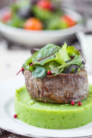 Grilled beef steak, green mashed potatoes with peas, herbs, beautiful presentation in restaurant photo