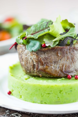 Grilled beef steak, green mashed potatoes with peas, herbs, beautiful presentation, tasty dish photo
