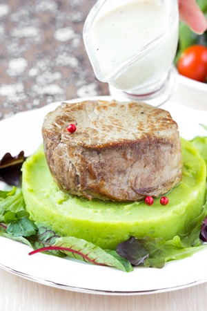 Grilled beef steak, green mashed potatoes with peas, herbs, pour out sauce photo