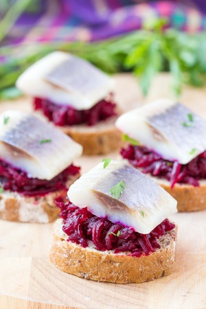 Canape herring with beets on rye toast, lemon and parsley, delicious starter, appertiser photo