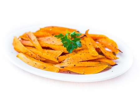 Sweet potatoes, batata, sliced, fried with spices, herb on plate, isolated