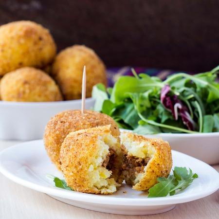 Italiaans voorgerecht arancini, rijst ballen gevuld met vlees gekookt in diepe vet