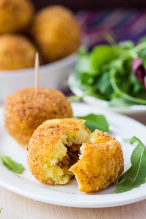 Italian appetizer arancini, rice balls stuffed with meat cooked in deep fat photo