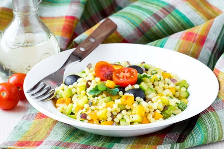 Israeli couscous ptitim with vegetables, zucchini, peppers, tomatoes, parsley, vegetarian diet healthy summer dish