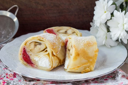 toppings: Tasty pancake rolls with three toppings, cheese, strawberries, banana, Shrovetide Stock Photo