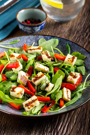 Salad with grilled cheese, spinach, tomatoes, pepper, paprika, delicious lunch diet dish