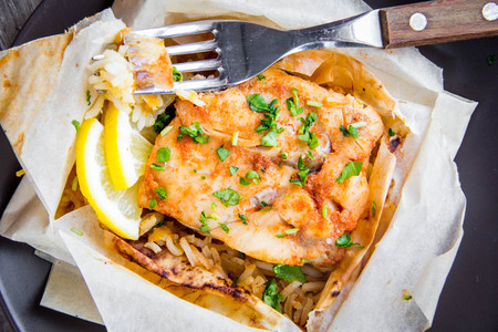 White fish fillet baked in parchment with rice and vegetables, delicious healthy dish, diet food
