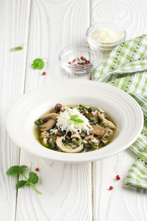 Healthy soup with spinach, chicken, rice, mushrooms and feta cheese, delicious lunch, diet food