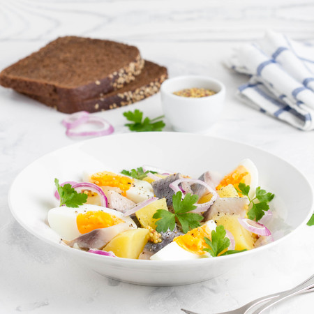 Potato salad with herring, egg, onion, tasty snack with mustard in a white plate Stockfoto