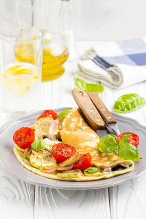 Thin rolled omelet with fried vegetables, zucchini, tomato, onion, mushrooms, delicious healthy Breakfast, 写真素材