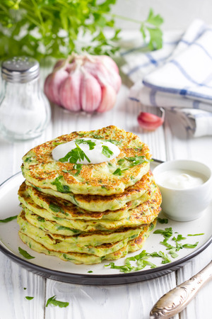 Zucchini pancakes with parsley and sour cream, summer food, delicious snack. High stack in a plate on white wood