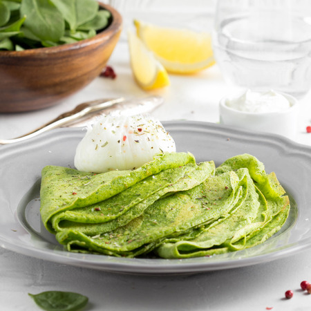 Green thin pancakes with spinach, poached egg, sour cream, lemon and aromatic herbs, delicious healthy food, Breakfast