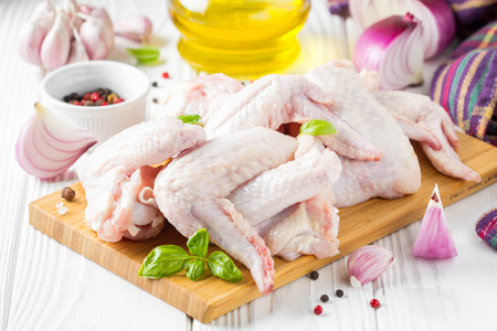 Raw chicken wings on a cutting board. Ingredients for cooking, spices, onion, oil and garlic