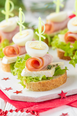Christmas canapes on bread with brie or Camembert cheese, ham and boiled quail egg. Beautiful presentation on the festive new years table. Delicious starter on stick