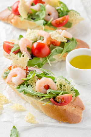 Bruschetta with arugula, shrimp, cherry tomatoes, cheese chips and balsamic. Three delicious open sandwiches for lunch
