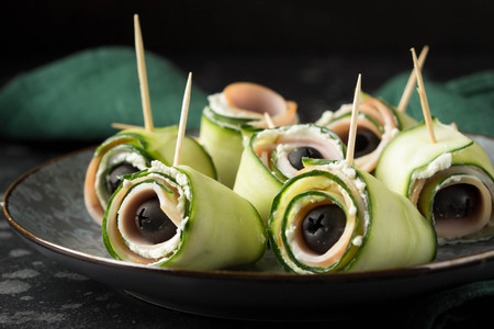 Cucumber roll with ham, cream cheese and black olive. Imagens