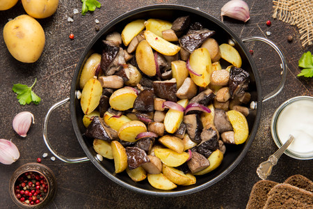 Fried potatoes with forest mushrooms, boletus, onions and sour cream.