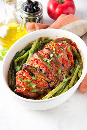 Baked whole pork meat with tomatoes, green beans and black olives, homemade cozy winter dish in a pot. Stock Photo