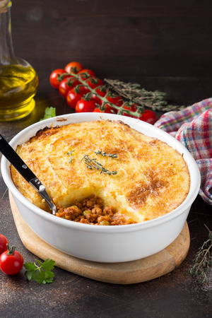 Shepherds pie with a brown crust, meat tomato stew with green peas and mashed potatoes with cheese. Delicious food, home cooking