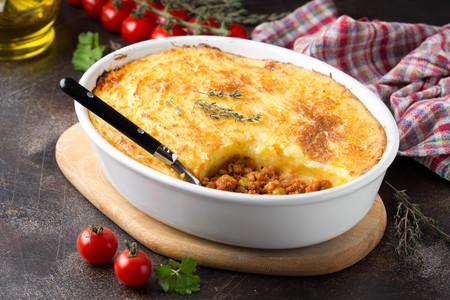 Shepherds pie with a brown crust, meat tomato stew with green peas and mashed potatoes with cheese. Delicious food, home cooking Фото со стока