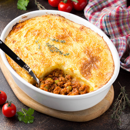 Shepherds pie with a brown crust, meat tomato stew with green peas and mashed potatoes with cheese. Delicious food, home cooking Stock Photo