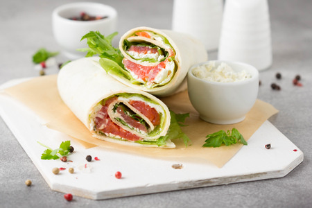 Tortilla with salmon, lettuce and cream cheese. Delicious snack wraps with fish and salad. Healthy burrito with pita bread for breakfast Stock Photo