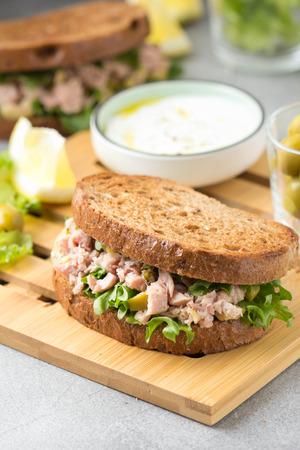 Sándwich de atún, aceitunas y limón. Delicioso almuerzo, comida sana, snack con pescado sobre tostadas crujientes.