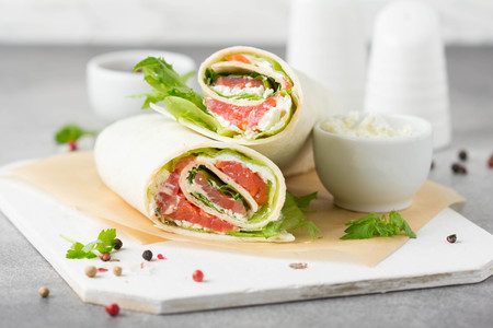 Tortilla with salmon, lettuce and cream cheese. Delicious snack wraps with fish and salad. Healthy burrito with pita bread for breakfast