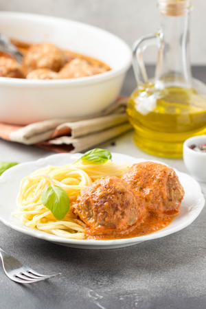 Meatballs in tomato sauce with cheese and pasta spaghetti, baked pork and beef cutlets in baking dish. Delicious homemade food