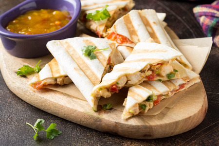 Quesadilla mexicana con pollo, tomate, queso y salsa a la parrilla. Aperitivo sabroso en un pellet, comida sana Foto de archivo
