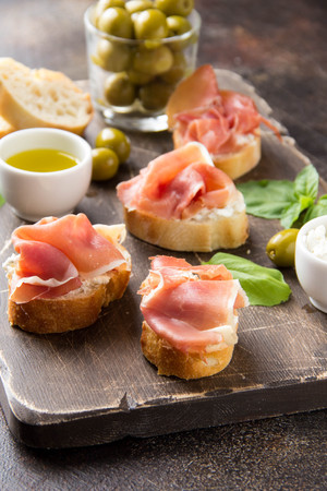 Toast with serrano ham (jamon, prosciutto crudo, hamon), traditional Italian antipasti. Delicious snack with bread, cream cheese, olives. Health food, appetizer for wine, bruschetta
