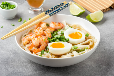 Japanese soup with wheat noodles, fried shrimp, soft-boiled egg with liquid yolk and green onions. Traditional Asian ramen, delicious lunch, healthy food