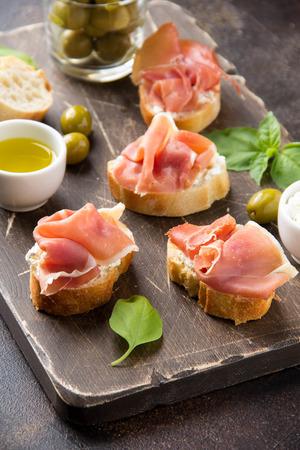 Toast with serrano ham (jamon, prosciutto crudo, hamon), traditional Italian antipasti. Delicious snack with bread, cream cheese, olives. Health food, appetizer for wine, bruschetta Imagens - 121756939