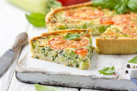 Quiche with vegetables (squash, tomatoes, cheese, herbs, green onions), open tart, French cuisine, traditional pastries, tasty