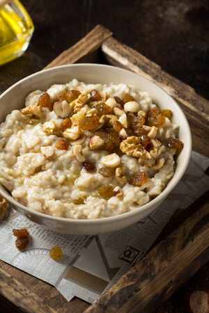 Oatmeal with nuts (hazelnuts, walnuts) and honey, porridge for Breakfast. Tasty and healthy food