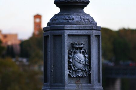 Detail of cast iron lamp on a bridge in Rome, panorama of the city in the background