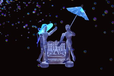 Pair of mannequins, she with straw hat and he with parasol. Background with miniature of the Trevi Fountain in Rome, rain of small colored bubbles. Invert colors effect, dark background.