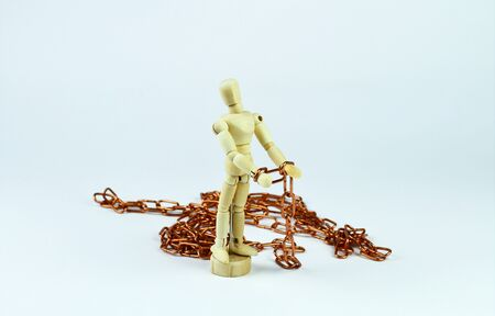 Wooden mannequin with hands tied by a copper chain. Light background