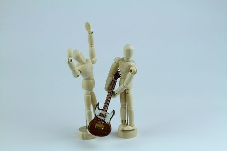Two wooden mannequin with scale reproduction of electric guitar. Light background