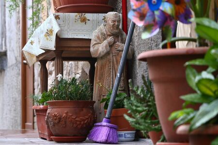 Image from the ground of the door of an Italian village house, statue of San Pio in the midst of household objects