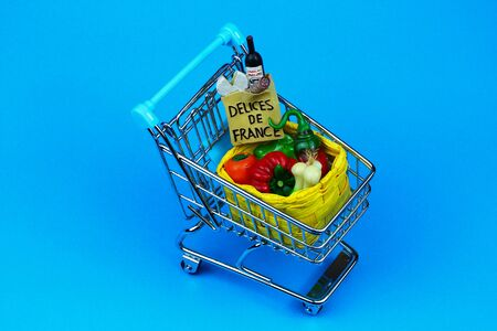 Overhead photo supermarket cart with bag of typical French products and a straw basket full of fresh vegetables. Light blue background.