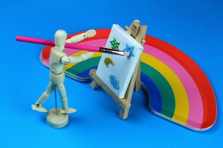 Wooden mannequin seen from above with brush in hand while painting on canvas. Light blue background with rainbow.