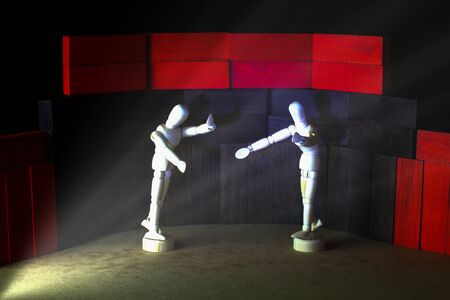 Pair of wooden mannequins who are acting in the theater. Plywood floor and black background.