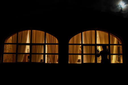 Illuminated windows of country house, figure of woman against the light. Diffused yellow light.
